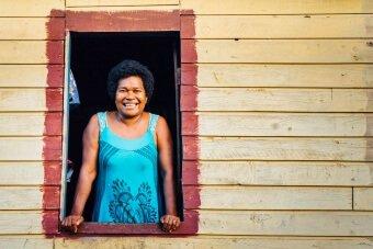 Femme fidjienne souriante à sa fenêtre